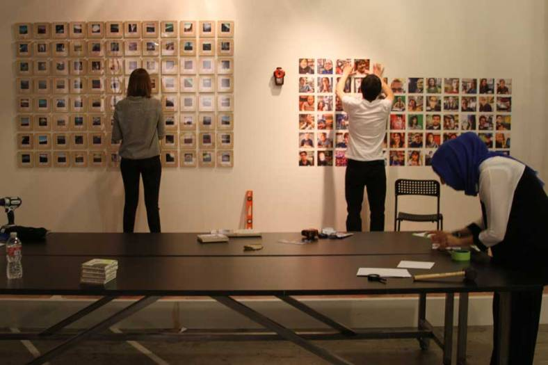 Intersection for the Arts interns install the 100 Days, 100 Portraits prints alongside the work of artist Joan Osato in late October for the Califas Festival, which runs Nov. 1-17 in San Francisco. (Photo by Rebecca Ahrens)